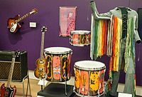 """A selection of instruments used by the Who, including a Rickenbacker and Gibson SG Special guitar, and Moon's """"Pictures of Lily"""" drum kit from Premier"""