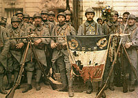 French Poilus posing with their war-torn flag in 1917, during World War I
