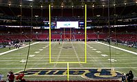A football field as seen from behind one end zone. The tall, yellow goal posts mark where the ball must pass for a successful field goal or extra point. The large, rectangular area marked with the team name is the end zone