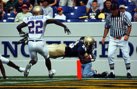 A player for the Navy Midshipmen (dark jersey) scores a touchdown while a defender from the Tulsa Golden Hurricane (in white) looks on. The goal line is marked by the small orange pylon