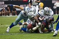 Dallas Cowboys defensive players force Houston Texans running back Arian Foster to fumble the ball