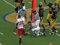 Officials use the chains to measure for a first down. Here, the ball is just short of the pole and therefore short of a first down.