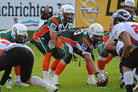 A quarterback for the Kiel Baltic Hurricanes under center, ready to take the snap
