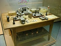 This was touted for many years as the table and experimental apparatus with which Otto Hahn discovered nuclear fission in 1938. The table and instruments are representative of the ones used, but not necessarily the originals, and would not have been together on the one table in the same room. Pressure from historians, scientists and feminists caused the museum to alter the display in 1988 to acknowledge Lise Meitner, Otto Frisch and Fritz Strassmann.