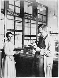 """Hahn and Meitner, 1913, in the chemical laboratory of the Kaiser Wilhelm Institute for Chemistry. When a colleague she did not recognise said that they had met before, Meitner replied: """"You probably mistake me for Professor Hahn."""""""
