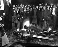 A group of white men pose for a 1919 photograph as they stand over the black victim Will Brown who had been lynched and had his body mutilated and burned during the Omaha race riot of 1919 in Omaha, Nebraska. Postcards and photographs of lynchings were popular souvenirs in the U.S.