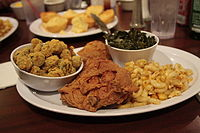 A traditional soul food dinner consisting of fried chicken with macaroni and cheese, collard greens, breaded fried okra and cornbread