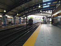 A Blue Line train approaches the northbound platform (left) at Airport station; the southbound platform is on the right side of the image.