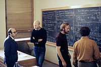 Discussion in the main lecture hall at the École de Physique des Houches (Les Houches Physics School), 1972. From left, Yuval Ne'eman, Bryce DeWitt, Thorne, Demetrios Christodoulou.