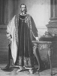 Franz Joseph in the regalia of the Order of the Golden Fleece, with the Bohemian Crown Jewels next to him. Painting by Eduard von Engerth for the Bohemian Diet, 1861.