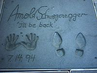 """Footprints and handprints of Arnold Schwarzenegger in front of the Grauman's Chinese Theatre, with his catchphrase """"I'll be back"""" written in."""