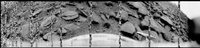 180-degree panorama of Venus' surface from the Soviet Venera 9 lander, 1975. Black-and-white image of barren, black, slate-like rocks against a flat sky. The ground and the probe are the focus. Several lines are missing due to a simultaneous transmission of the scientific data.