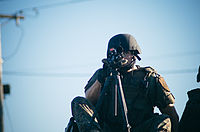 Police sharpshooter atop a SWAT vehicle during protests at Ferguson