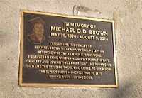 Bronze plaque in memory of Michael Brown on sidewalk where shooting incident occurred