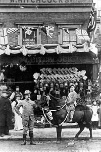 """William Hitchcock, probably with his first son, William, outside the family shop in London, c.undefined 1900; the sign above the store says """"W. Hitchcock"""". The Hitchcocks used the pony to deliver groceries."""