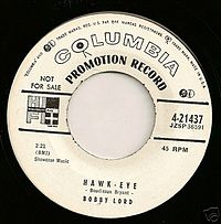"""Transitional 1955 promo 45 r.p.m. label showing both the old """"notes and mike"""" and new """"walking eye"""" logos"""
