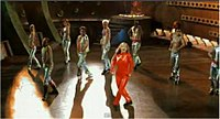 Spears dances around wearing a red bodysuit while surrounded by backup dancers in futuristic outfits during the music video.