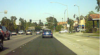 A typical stretch of Valencia Boulevard in the Valencia part of Santa Clarita in July 2004. The bridge in the distance carries a paseo (a type of dedicated pedestrian pathway) over the roadway.
