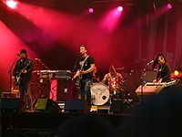 The band performing live, August 25, 2005 in Paris, France. Included in this performance are two bandmates from the band Eleven, Alain Johannes and the late Natasha Shneider, who joined the line-up for Lullabies to Paralyze and the supporting tour.