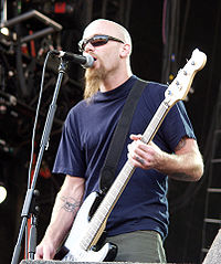 Nick Oliveri, bassist 1998–2004, performing with the band at the 2003 V Festival