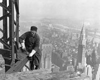 A construction worker atop the Empire State Building as it was being built in 1930. The Chrysler Building is behind him.