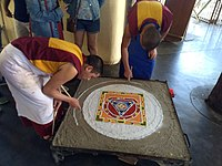 Buddhist Monks performing traditional Sand mandala made from coloured sand
