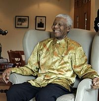 """Mandela on a visit to Australia in 2009; he is wearing one of the brightly coloured garments that became known as """"Madiba shirts"""""""