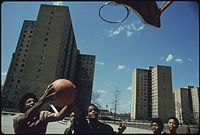 African-American youths play basketball in Chicago's Stateway Gardens high-rise housing project in 1973.