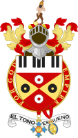 "Sir Elton John's coat of arms. Granted to him in 1987, the shield includes piano keys and records. The Spanish motto, el tono es bueno, combines a pun on Elton John's name with the translation ""the tone is good"". The black, red and gold colours are also those of Watford F.C. The steel helmet above the shield faced forwards and with its visor open indicates that John is a knight."