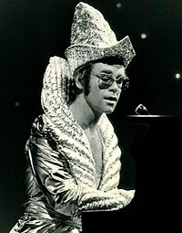 Elton John often wore elaborate stage costumes as part of the glam rock era in the UK music scene.
