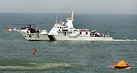 Indian Coast Guard (ICG) helicopter takes a survivor to an ICG ship during a mock drill