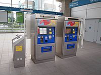 A ticket vending machine (right), next to an old faresaver validator