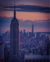 The Empire State Building in the foreground looking southward from the top of Rockefeller Center, with One World Trade Center in the background, at sunset. The Midtown South Community Council acts as a civic caretaker for much of the neighborhood between the skyscrapers of Midtown and Lower Manhattan.