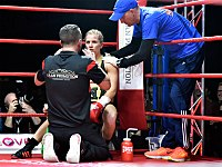 Boxer Tina Rupprecht receiving instructions from her trainer while being treated by her cutman in the ring corner between rounds.