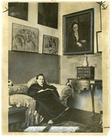 Stein in her Paris studio, with a portrait of her by Pablo Picasso, and other modern art paintings hanging on the wall (before 1910)