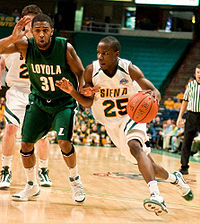 Siena guard Ronald Moore dribbles toward the basket in a game against Loyola in January 2010.
