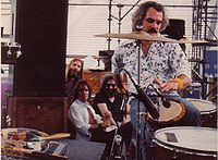 Grateful Dead members in the early 1980s: Brent Mydland, Bob Weir, and Jerry Garcia watch Bill Kreutzmann play the drums. Not pictured are Phil Lesh and Mickey Hart.
