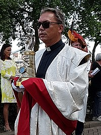 A priest carrying an arm reliquary