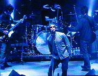 """Oasis playing live. NME states, """"as (What's the Story) Morning Glory? emerged to colossal sales, it became clear that while Blur had won the battle, Oasis were winning the war."""""""