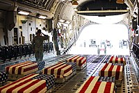 Coffins of soldiers killed in the 2009 Fort Hood shooting being loaded aboard an aircraft for flight to Dover Air Force Base, 6 November 2009.