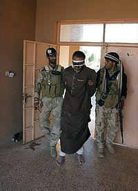 Iraqi troops or Popular Mobilization Forces militiaman with a captured ISIL terrorist in Salahuddin campaign in Iraq, 6 April 2015.