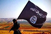 ISIL terrorist carrying the group's flag on a hill overlooking the town of Dabiq in Syria, 2014.