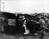 A woman and her child outside their bombed home in Ebisu, Tokyo following the war