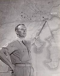 Brigadier General Haywood S. Hansell posing with a map of the Tokyo region in November 1944