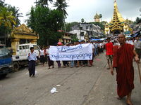 Protesters in Yangon during the 2007 Saffron Revolution with a banner that reads non-violence: national movement in Burmese. In the background is Shwedagon Pagoda.