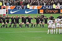 """A haka performed by the national rugby union team (""""All Blacks"""") before a game. The haka is a challenge with vigorous movements and stamping of the feet."""