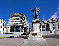 """A statue of Richard Seddon, the """"Beehive"""" (Executive Wing), and Parliament House (right), in Parliament Grounds, Wellington."""