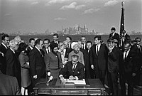 President Lyndon B. Johnson signs the Immigration Act of 1965 as Vice President Hubert Humphrey, Senators Edward M. Kennedy and Robert F. Kennedy and others look on.