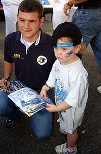 Atwood posing with a young fan at Dover in 2004, courtesy of the U.S. Navy
