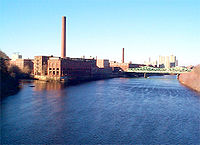 The Massachusetts Mill at the confluence of the Merrimack and Concord Rivers; across the Cox Bridge are the Boott Mills; in the upper left is the historic Lowell Sun building with its iconic sign on top.